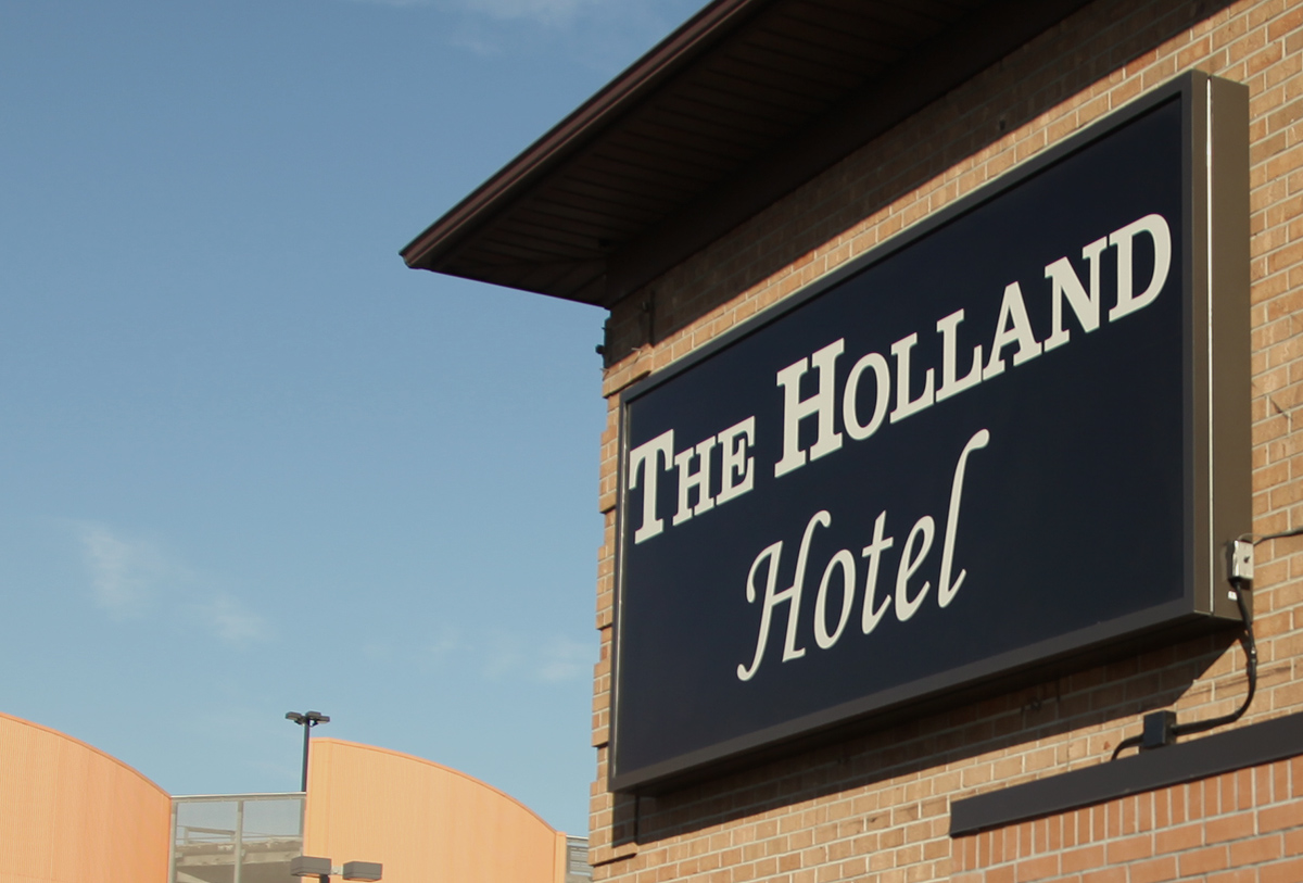 The Holland Hotel exterior sign on tan brick building