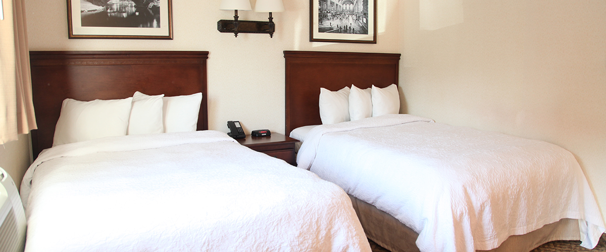hotel room with 2 beds with white comforter and pillows next to wall lamps