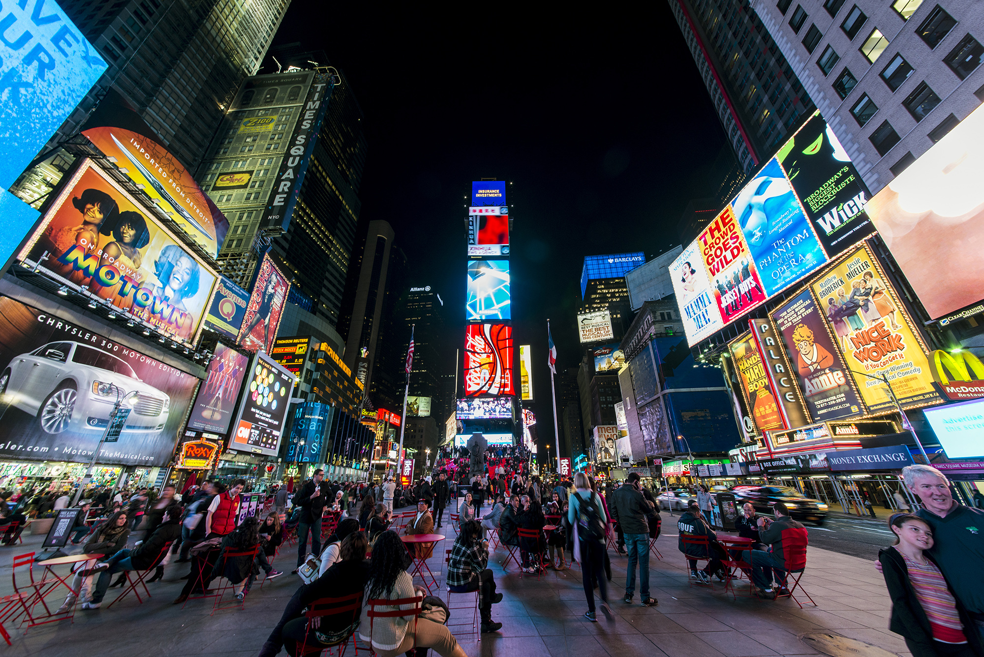 lively times square with large buildings, bright lights, and people sitting and walking