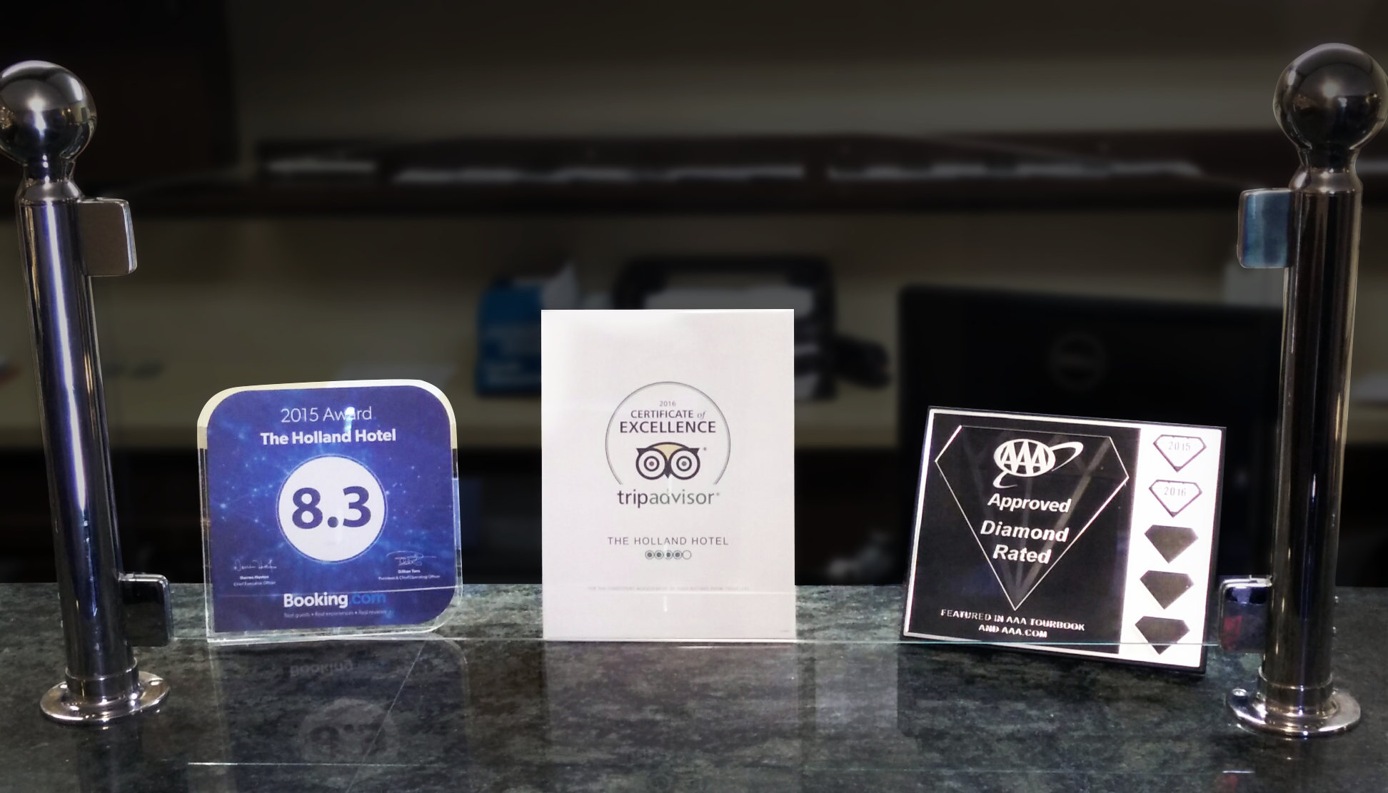 the holland hotel awards on desk from booking.com, TripAdvisor, and triple A