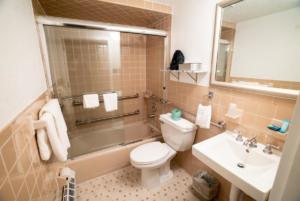 hotel bathroom with sink, toilet, and shower with bathtub